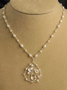 Ethereal Pendant Necklace with white pearls, white topaz, and moonstone. Has matching earrings.