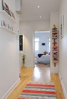 gostei do piso de madeira, do tapete, das prateleiras com livros deitados.