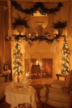 Christmas glow...2 trees on either side of fireplace, with draped greenery garland on mantel and lights entwined in that as well as the trees - LOVE!