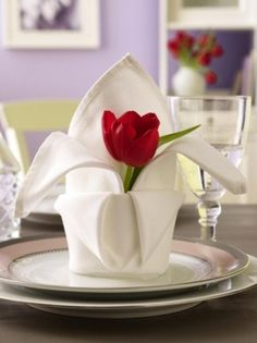 White Napkin folded into a cup or vase and holds a single bloom. Picture shows a red tulip.  Choose flowers with strong, woody, sturdy, stems that so it stays upright. Options: rose bud, orchid, peonies, lilies, mums, lilacs.