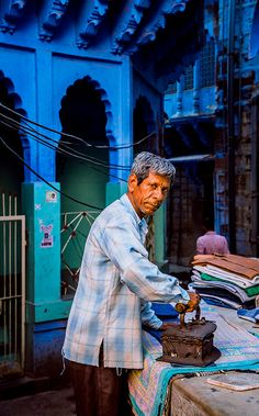 INDIA: Laundry with gentleman at work open air.