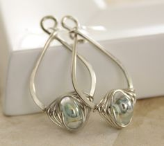 Pear shape silver earrings with herringbone wrapped luster aquamarine color lampwork glass. $26.00, via Etsy.