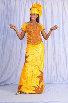 A form fitting orange African brocade blouse with brown embroidery Comes with a wrap skirt and fabric for head wrap.    Estimated delivery