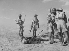 British soldiers, armed with an Thompson M1928 and Lee-Enfields Mk Is, inspect an Akrika Korps motorcyclist's MP40 SMG in the Tunisian desert 1942