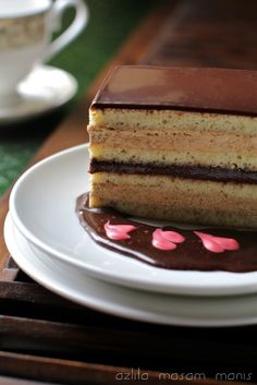 """Opera Cake is a type of French cake. It is made with layers of almond sponge cake (known as Joconde in French) soaked in coffee syrup, layered with ganache and coffee buttercream, and covered in a chocolate glaze. According to Larousse Gastronomique """"Opéra gateau is an elaborate almond sponge cake with a coffee and chocolate filling and icing."""" The cake was popularized by the French pâtisserie house Dalloyau."""