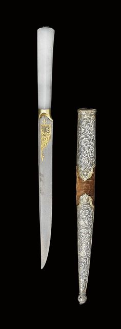 AN OTTOMAN JADE HANDLED KNIFE   TURKEY, 18TH CENTURY   The single-edged watered steel blade with flat spine, each side with gold damascened inscription cartouche, with gilt collar above and light jade handle with single inset turquoise stone at the top, the brown velvet-covered wooden sheath with repoussé silver gilt mounts worked with scrolling arabesques  12¼in. (31.7cm.) long