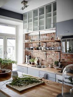 Cozinha com parede de tijolos aparentes.