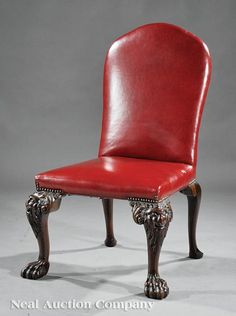 An Irish Georgian Carved Mahogany Back Stool, probably 19th c., arched back, trapezoidal seat, mask carved cabriole legs ending in paw feet, red leather upholstery.