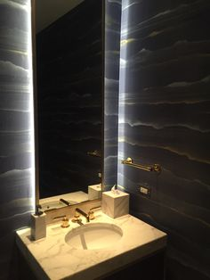 Custom Bathroom vanity with white marble counter, Waterworks brass fittings and custom backlit mirror with LED lights