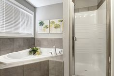 Master bedroom ensuite with stand up shower, soaker tub. jet tub with tile surround and grey tile flooring. Master bathroom.