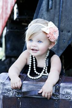 this baby girl is so adorable with her headband and pearls!
