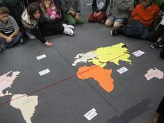 Hands on geography!!  The teacher is reviewing latitude, longitude, hemispheres, continent and ocean names and cardinal/intermediate directions. Students use yarn for the Prime Meridian and Equator, and index cards with the names for the oceans. Then the class uses unifix cubes to mark all the spots they are responsible for being able to locate.
