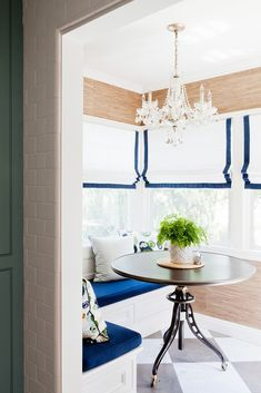 Breakfast nook with white roman shades with blue trim, crystal chandelier and built-in banquet with cobalt blue velvet cushions