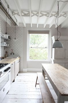 worn wooden floors, beams along the ceiling and long wooden table in the kitchen