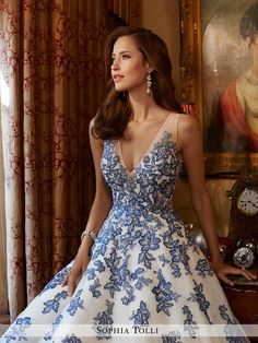 Sophia Tolli - Y11701 Ciel - Sleeveless light tulle over sparkling sequin full A-line gown adorned with hand-beaded lace appliqués and scattered sequins, deep V-neckline with semi-sheer peekaboo, illusion shoulder straps and sides, illusion back features matching appliqués and zipper trimmed with diamante buttons, chapel train length.Also available with solid back lining as Y11701SB.Sizes: 0 - 28Colors: Ivory/French Beige, Ivory/Sapphire, Diamond White
