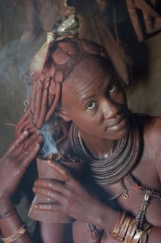 The Himba people (Namibia): 'Himba women are famous for smearing themselves with a fragrant mixture of ochre, butter and bush herbs, which dyes their skin a burnt-orange hue.' http://www.lonelyplanet.com/namibia