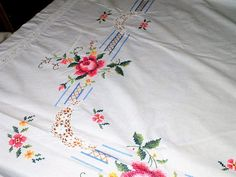 Beautiful Vintage White Cotton Very Large ( 260cm x 165cm) Hand Embroidered Cross Stitch Tablecloth Made of white cotton fabric with hand stitched roses and small flowers. a crocheted cotton design around the cloth and cut out patterning at the corners. The tablecloth is in