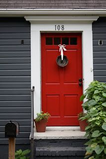 red door, white frame on dark blue house. LOVE this