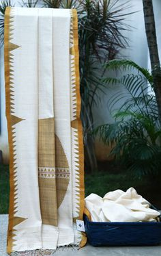 An off-white khadi and tussar silk mix by Vriksh. The saree has a simple temple border that combines nicely with the large circular motif on the pallu, the star of the piece