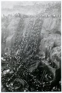 The side of the open-pit gold mine is a labyrinth of workers climbing the narrow trails with their heavy loads of earth. garimpeiros - prospectors.