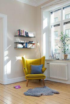 un joli canapé jaune et sol en planchers en bois clair