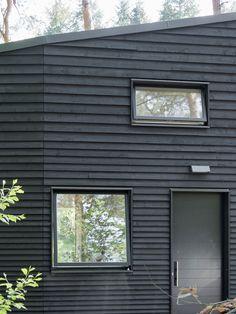 Thin external wood architraves around black aluminium windows, on a weatherboard house.