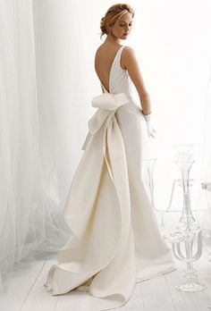 A sleeveless ballgown wedding dress with an open back and large bow.