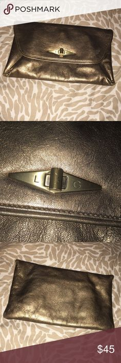 Lulu Guinness clutch Bronze leather clutch with turnlock closure and multiple pockets. Fabric lining. Slight scuffing on front as seen in last picture. Gently used. Priced accordingly. Lulu Guinness Bags Clutches & Wristlets