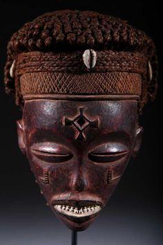 Masque Tchokwé - Le masque Cihongo est la version masculine du masque Mwana Pwo. Les similitudes de style sont évidentes dans le traitement des traits du visage : le grand front bombé, dégagé, marqué de la croix de Saint André, les oreilles parfois ornées de boucles de métal, les yeux mi-clos et les marques de« larmes », la même forme du nez, la bouche aux dents épointées mise en valeur. Le Cihongo est la représentation d'un esprit masculin évoquant puissance et richesse.
