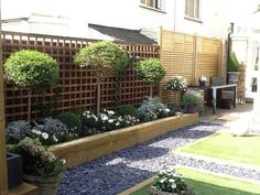 Raised sleeper border with trellis/standards/slate path/timber edge to lawn