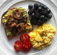 Wholemeal toast with smashed avocado and grilled mushrooms with tomatoes, scrambled eggs, blackberries and blueberries.