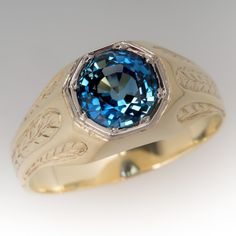 1940's Mens 1.8 Carat Greenish Blue Sapphire Ring 18K This awesome vintage mens ring features a stunning 1.81 carat no heat natural sapphire in a bold engraved mounting. The sapphire is an intriguing icy greenish blue color. The ring is crafted of 18k yellow gold