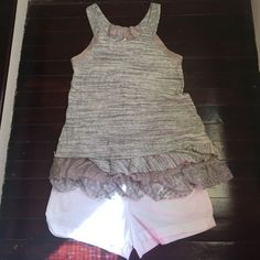 Free People Tank Top Stay cool this summer in this Free People Tank top with ruffle bottom detail. Light grey with light pink and sparkly detail on straps and ruffles. Small size. Never worn. Excellent condition. Free People Tops Tank Tops