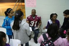 Veteran Racine Raiders running back Marcus Baskin signs autographs for students at Julian Thomas Elementary School as part of the Reading with the Raiders program.