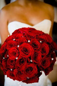 """This single-variety wedding bouquet has luxurious red roses and floral pins to give it that extra """"bling."""" This look not only stands out, but it steals the show for the ultimate romantic experience. Achieve this look using wholesale roses and your bouquet will be as big as you can carry! #weddingbouquet #roses #redroses"""