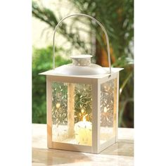 """Large White Lantern: When lit from within by candlelight, these old-fashioned lanterns are a true delight! The panels' gracefully curling vine design takes on a magical glow. Perfect for adding special sparkle to your next garden party! Candle not included. Metal and glass. 5 3/4"""" diameter x 8"""" high. Fits a 3 1/2"""" candle"""
