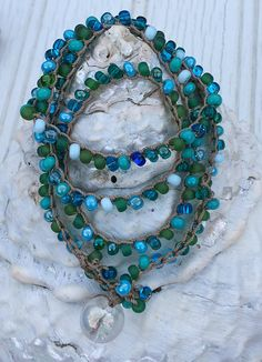 Crocheted Necklace This necklace is 24.5 finished length May be worn as a necklace or a wrap bracelet The various colored blue, green and white seed beads are crocheted on a brown nylon bead cord. The necklace has a glass bead & loop fastener. A great pop of color for that summer outfit