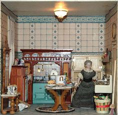 """On the left, the kitchen has a very interesting stove and icebox (with """"real ice"""" in the upper compartment) a sink with dishes drying on it, a sack of flour and a busy cook.  In the middle of the kitchen is an antique Biedermeier marble-topped table covered with different foods: a roasted turkey, two plates with lamb chops on them, a pot-au-feu, a cutting board with potatoes that are being peeled, and a cherry pie. A large basket full of vegetables sits on the floor next to the table."""