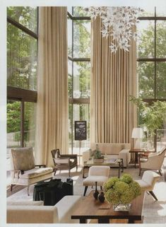 Two Story Ivory linen drapes allow the option of privacy or an open view. They make this large great room with high ceilings feel cozy.