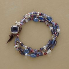 """SERENA BRACELET--Serene blue hues warmed by garnets and copper beads encircle the wrist on three sequenced strands. A prominent iolite cabochon wrapped in sterling silver joins with a leather loop. Also includes kyanite, pyrite, aquamarine, agate and labradorite. Handmade exclusive. Approx. 7-1/4""""L."""