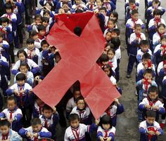 Primary school students present red ribbons during an event on the eve of the World AIDS Day in Wuyuan, in southern China's Jiangxi province, Nov. 30, 2011. China will have about 780,000 people infected with the AIDS virus by the end of this year, state media reports, with most having contracted it through heterosexual sex. (Associated Press)