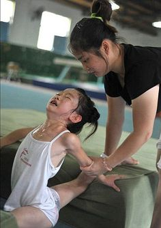 Sweat and tears: A young girl is pushed through a tough gymnastics exercise.  I will reserve comment - just read the article.