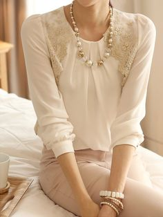 Long-sleeved lace blouse, feminine details, and skirt.