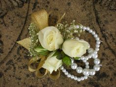 Wrist corsages: white spray roses, baby's breath, and green hypericum with gold and pearl accents.