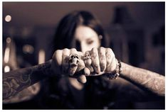 skull rings on hands with tattoos