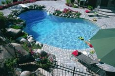 Swimming Pool: Amazing Stone Pool Deck Design Ouutdoor Private Pool Design Ideas With Paving Stone Deck Also Metal Fence And Grey Pool Chair Also Big Green Umberella : Mesmerizing Stone Pool Deck Design Ideas