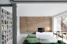 """A entrada se dá por uma sala semi-fechada, de onde já se pode ter uma visão geral do restante do lugar. Um sofá de veludo verde e duas cadeiras vintage compõem a decoração, junto com a estante que faz a divisão da sala com o quarto. A parede de tijolo nu, segundo a autora, é """"um lembrete arqueológico"""". A cozinha aberta é o próximo ambiente, ponto focal do projeto, se conectando com a sala de jantar e o quarto principal."""