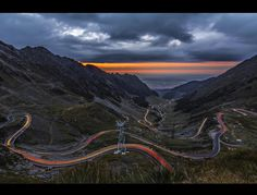 The TransFagarasan - The Transfăgărășan (trans (over, across) + Făgăraș) or DN7C is the second-highest paved road in Romania. Built as a strategic military route, the 90 km of twists and turns run north to south across the tallest sections of the Southern Carpathians, between the highest peak in the country, Moldoveanu, and the second highest, Negoiu. The road connects the historic regions of Transylvania and Wallachia, and the cities of Sibiu and Pitești.The road climbs to 2,034 metres…