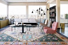 A contemporary living space with matching armchairs and Persian rug // Italian design