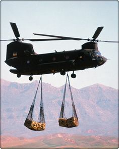"""""""The Chinook is a multi-mission, heavy-lift transport helicopter. Its primary mission is to move troops, artillery, ammunition, fuel, water, barrier materials, supplies and equipment on the battlefield. Its secondary missions include medical evacuation, disaster relief, search and rescue, aircraft recovery, fire fighting, parachute drops, heavy construction and civil development."""" Chinook in flight carrying cargo (Neg#: DVD-1100-2)"""